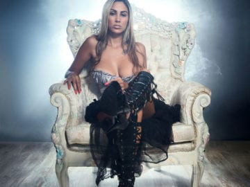 Sexy Queen Sitting Upon her Gray Padded Throne